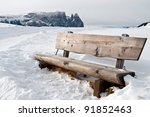 Isolated Wooden Bench On Snow...