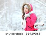 ice skating winter woman holding ice skates outdoors in snow. Beautiful young mixed race chinese asian / caucasian woman - stock photo