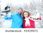 Ice skating winter couple smiling happy and excited showing ice skates outdoors in snow. Beautiful young multi-racial couple healthy lifestyle concept. - stock photo