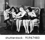Man dressed Napoleon surrounded by young women - stock photo
