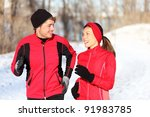 Couple running in winter snow living healthy lifestyle. Man and woman runner in their 20s. Young multi-ethnic couple, Asian woman, Caucasian man. - stock photo