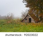 Shattered recreational shed in foggy landscape - stock photo