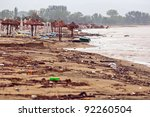 A dirty polluted beach  in the rain - stock photo