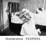 Nurse praying for an outlaw lying in bed - stock photo