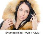 The beautiful girl in a fur hood - stock photo