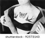 Close-up of a woman showing tattoos on her chest - stock photo