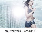 Young woman running in front of urban style - stock photo