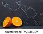 Structural formula of vitamin C on blackboard with orange - stock photo
