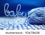 baby word made of yarn among blue textile - stock photo