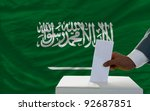 man putting ballot in a box during elections  in front of national flag of saudi arabia - stock photo