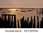 Dilapidated old weather worn pilings at sunrise on casco bay in portland maine - stock photo