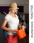 girl with a straw hat in a boutique - stock photo