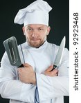 Chef in uniform posing with kitchen utensils, dark background - stock photo