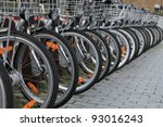 Row of city bicycles parked in a paved street.Selective focus on the first wheel. - stock photo