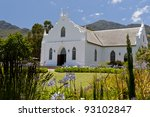 White church with mountain backdrop in Franschhoek, South Africa - stock photo
