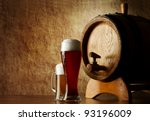 Beer into glass on a old stone and old barrel - stock photo
