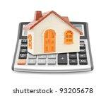 Small orange toy house on calculator - stock photo
