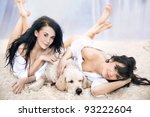 Smiling women lying on the carpet with dog - stock photo