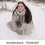 The girl in a fur coat throwing snow upwards - stock photo