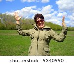 smiling woman. green grass, blue sky and clouds - stock photo