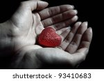 Woman hands holding a small heart as a symbol of love - stock photo
