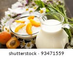 fresh cottage cheese on old wooden table and a jug of milk - stock photo