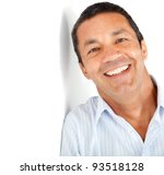 Happy latin man leaning against a white wall - stock photo