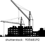 silhouettes of two cranes near...