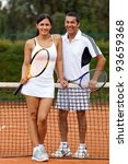 Couple at the court playing tennis and holding rackets - stock photo
