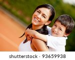 Lovely portrait of a mother and son at the tennis court - stock photo