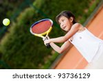 Little girl playing tennis at a clay court - stock photo