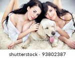 Two cute ladies with golden retriever dog - stock photo
