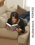 female teen on couch reading book - stock photo