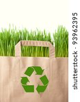 Recycling concept with grocery bag full of green grass - stock photo