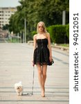 Stock photo young fashion woman walking her dog in the park 94012051