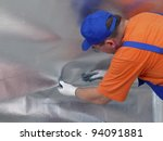 Construction worker affixing vapour insulation foil under thermally insulated attic surface - stock photo
