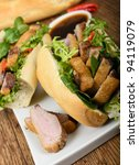Banh mi - Vietnamese tea smoked duck sandwich with salad and dipping sauce. - stock photo