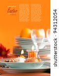 Restaurant menu series with copyspace. Easter table setting in orange tones with egg decoration, candles and flower - stock photo