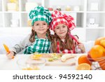 Little chef girls slicing fruits in the kitchen - healthy eating - stock photo