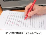Stock photo hand proofreading a manuscript beside laptop 94627420