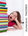 Young school girl looks shocked at a large stack of books - stock photo