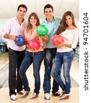 Happy group of friends bowling and holding balls - stock photo