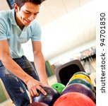Casual man picking up a bowling ball - stock photo