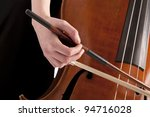 close-up on hand with bow playing the bass - stock photo