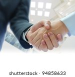 business people shaking hands  on indoor building background - stock photo