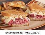 Grilled reuben sandwich with pastrami and swiss cheese on a plate - stock photo