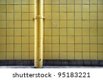 grunge tiled wall with painted metal pipe - stock photo