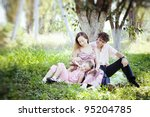 happy family sitting on the lawn in the apple garden - stock photo