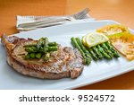 grilled beef steak with tomato slices and asparagus - stock photo