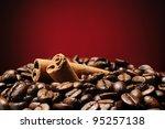 Heap of coffee beans with cinnamon sticks - stock photo